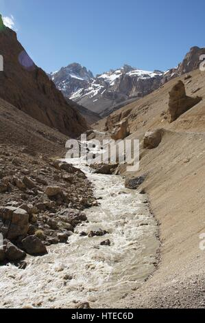 A view of melt-water and its mountain source in Kashmir, between Sarchu and Pang. - Stock Photo