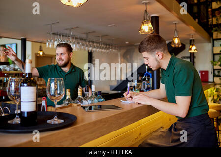 The barman barista  is working at  bar. The waiter writes order in a notepad. - Stock Photo