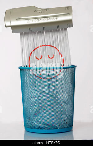 Destroy the sadness. Shredder documents with printed images concept thrown in the trash. White and blue basket. - Stock Photo