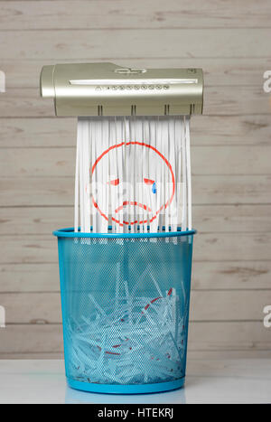 Destroy the sadness. Shredder documents with printed images concept thrown in the trash. White background and blue - Stock Photo