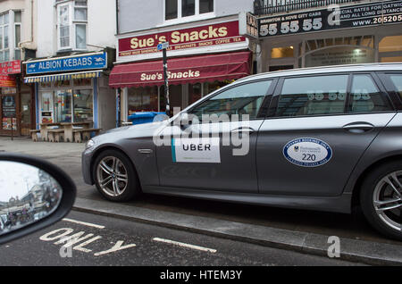 An Uber taxi parked on the pavement in Queens Road Brighton UK - Stock Photo