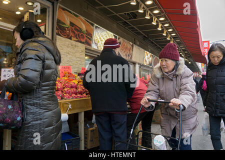 An older Chinese American woman pushing a cart near a fruit stand in CHinatown, Flushing, Queens, New York City. - Stock Photo