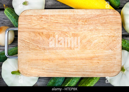 Cutting board, fresh vegetables on wooden table.  Top view with copy space. - Stock Photo