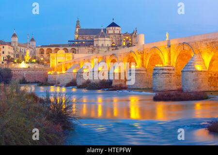 Illuminated Great Mosque Mezquita - Catedral de Cordoba with mirror reflection and Roman bridge across Guadalquivir - Stock Photo