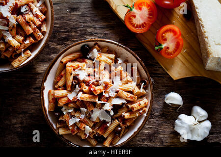 Couple of plates of rigatoni pasta with tomato sauce and olives - Stock Photo