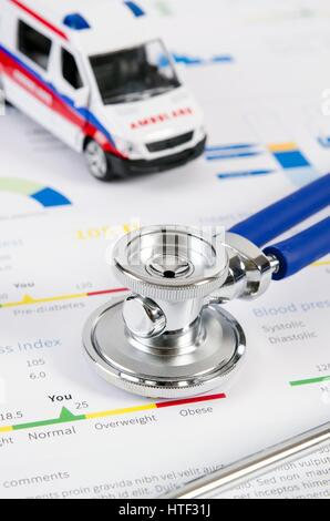 Health condition score report. Stethoscope on medical background with ambulance toy composition. - Stock Photo