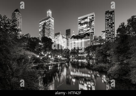 Midtown Manhattan skyscrapers illuminated in evening.The buildings of Central Park South are reflected in the Pond. - Stock Photo