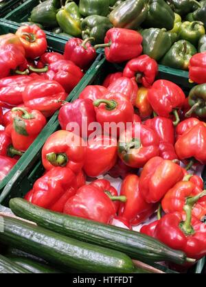 Red and green peppers in bulk on a market stall - Stock Photo