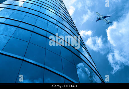 glass curtain wall and aircraft against a blue sky - Stock Photo