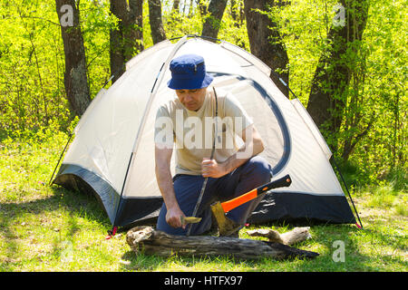Man chopping wood to tent - Stock Photo
