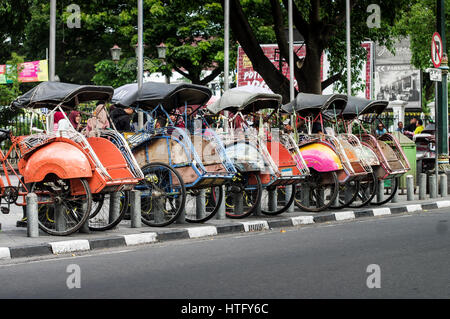 Becaks (bicycle taxis) parked along the road in Yogyakarta - Jave, Indonesia - Stock Photo