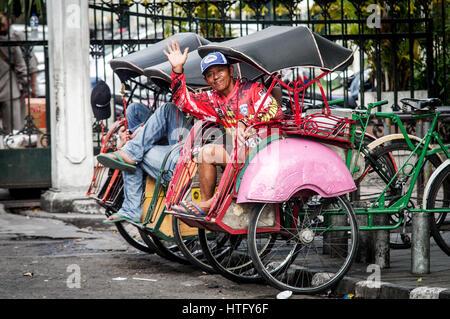 Friendly becak driver giving a wave in Yogyakarta - Java, Indonesia - Stock Photo