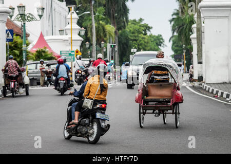 Mopeds and becaks in bustling central Yogyakarta - Java, Indonesia - Stock Photo