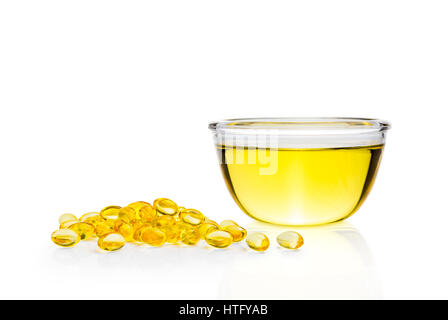 Yellow Sacha Inchi liquid, oil, in clear glass bowl and soft gel pills on white background with light reflection - Stock Photo