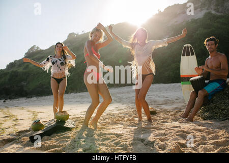 Happy friends enjoying on the beach and dancing. Young people having fun at beach party, women dancing and man playing - Stock Photo