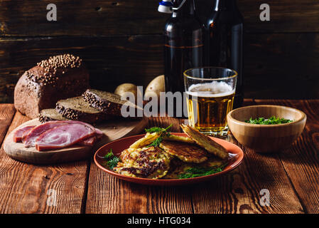Glass of Beer with Potato Pancakes, Smoked Meat and Rye Bread. - Stock Photo