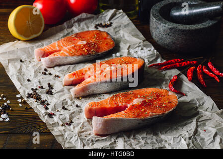 Three Salmon Steaks Prepared for Cooking with Chili Peppers and Other Spices. - Stock Photo