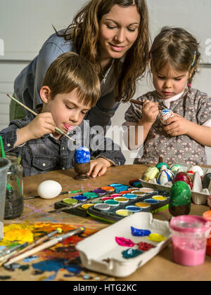 Photo of a mother and her children painting and decorating hard-boiled eggs for easter. - Stock Photo
