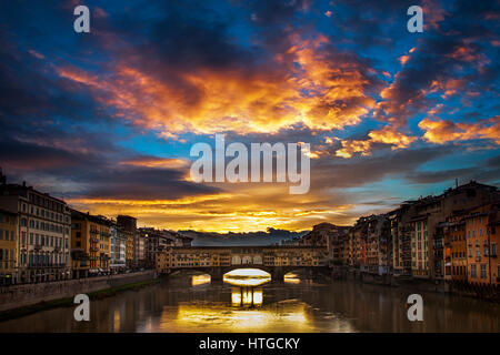 Clearing storm clouds at dawn create a dramatic sunrise over the Ponte Vecchio bridge in Florence, Italy - Stock Photo