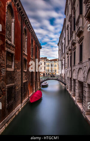 Long exposure of a quiet canal in Venice, Italy.  In the background is the Grand Canal. - Stock Photo