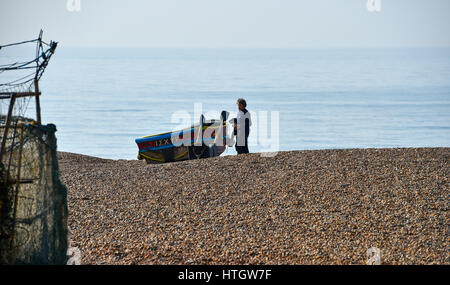 Brighton UK 15th March 2017 - A fisherman prepares his boat to go to sea in the calm before the storm in Brighton - Stock Photo