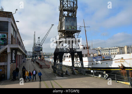 Bristol, UK. 15th March, 2017. UK Weather. People Stroll along the dockside on a mild day where in Bristol Big Screen - Stock Photo