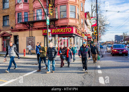 People cross street on green light, First and Commercial Drive, Vancouver, British Columbia, Canada. - Stock Photo