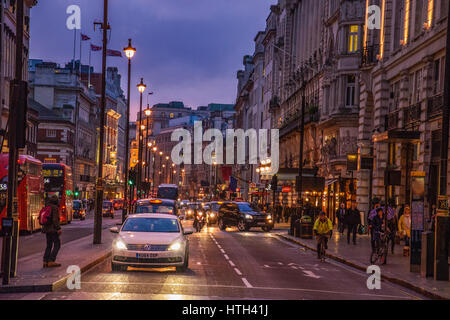 Wonderful cityscape view from central London. Traffic at Picadilly Circus square against a heavy cloudy sky. Street - Stock Photo