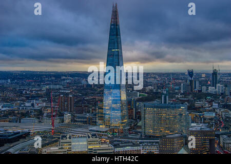 Panoramic aerial view of urban London with the Shard skyscraper and Thames river at sunset against a cloudy sky. - Stock Photo