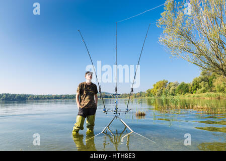 Fishing adventures, carp fishing. Fisherman and carpfishing gears. Angler with green waders on lake - Stock Photo