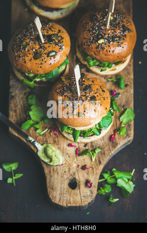 Healthy homemade vegan burger with beetroot-quinoa patty on wooden board - Stock Photo