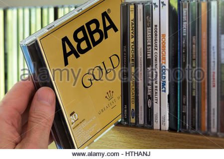 GOLD, ABBA  CD being chosen from a shelf of other CD's, England - Stock Photo