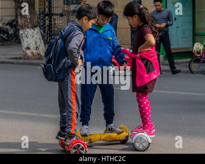 Children with parents playing on streets of Hanoi in Vietnam - Stock Photo