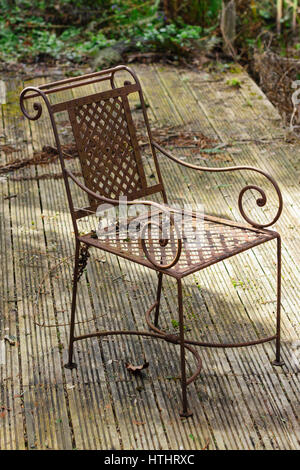 rusty abandoned chair on neglected wooden decking in an overgrown poorly maintained garden stock photo