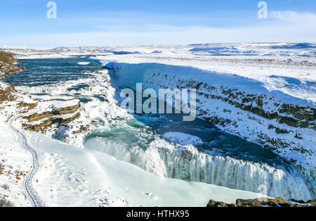 Looking over the edge of cliff to the two tier frozen waterfalls, Gullfoss, Golden Circle, Iceland - Stock Photo