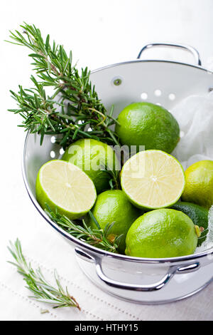 Fresh limes and rosemary springs in white enamel colander. - Stock Photo