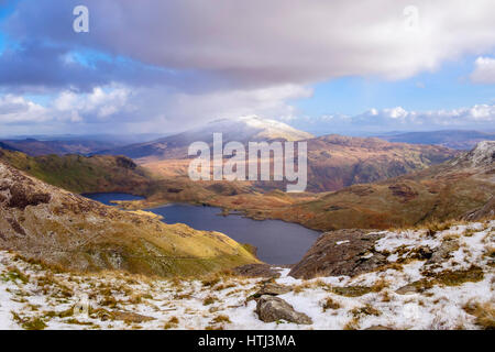 View to Llyn Llydaw lake and distant Moel Siabod from Y Gribin ridge in Snowdon horseshoe with snow in winter.  - Stock Photo