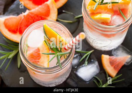 Refreshing summer drink with ice with rosemary and grapefruit on a stone background. The concept of eating vegetarians, - Stock Photo