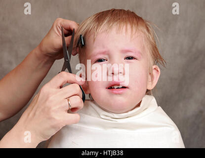 The child does not want to cut one's hair, his emotions - Stock Photo