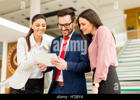 Smiling business team working on  tablet pcs - Stock Photo