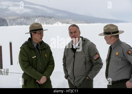 U.S. Secretary of the Interior Ryan Zinke, center, speaks with park rangers during a visit to Glacier National Park - Stock Photo