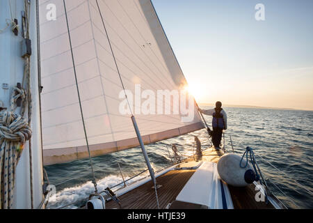 Man Standing On The Front Of Sail Boat In Sea - Stock Photo
