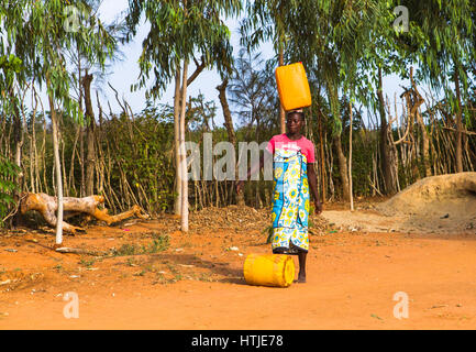 A young woman is carrying water from a nearest hydrant to her home. Malindi, Kenya. - Stock Photo