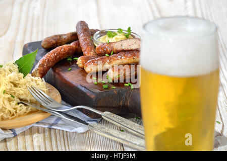 Fried Bavarian sausages from Nuremberg served with sauerkraut and a Munich lager beer - Stock Photo
