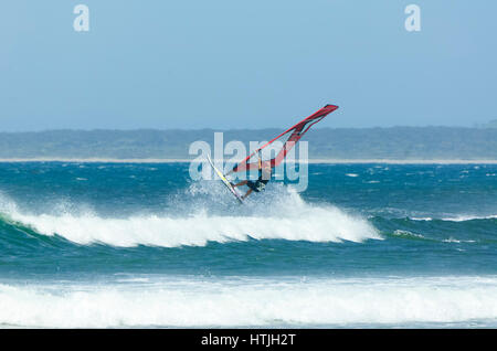 Windsurfer jumping over a big wave at Seven Mile Beach, Gerroa, Illawarra Coast, New South Wales, NSW, Australia - Stock Photo