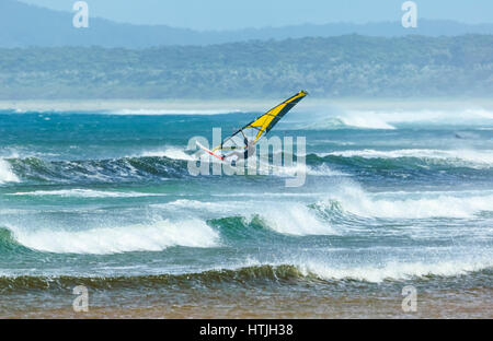 Windsurfer surfing in heavy seas with large waves at Seven Mile Beach, Gerroa, Illawarra Coast, New South Wales, - Stock Photo