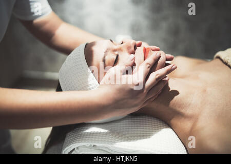 Masseuse massaging female who is relaxing at salon - Stock Photo