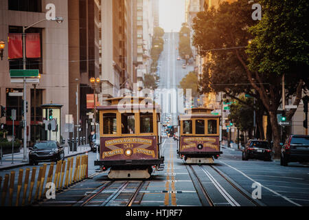 Classic view of historic traditional Cable Cars riding on famous California Street in early morning light at sunrise, - Stock Photo