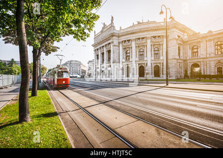 Famous Wiener Ringstrasse with historic Burgtheater (Imperial Court Theatre) and traditional red electric tram at - Stock Photo