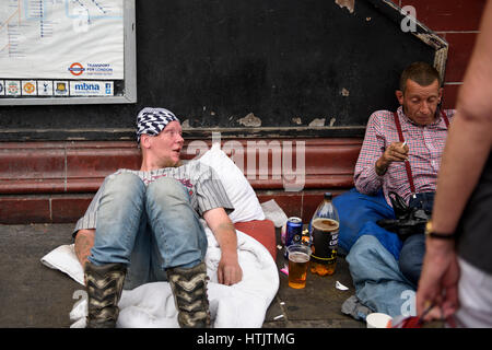 Men laying on the ground outside the Camden Town station - Stock Photo